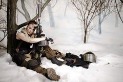 Das schöne Mädchen in einer Militäruniform mit der Waffe sitzt Lizenzfreies Stockfoto