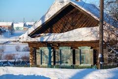 Das schneebedeckte alte Blockhaus mit hölzernen Fensterläden Dorf Visim, Russland Lizenzfreies Stockfoto