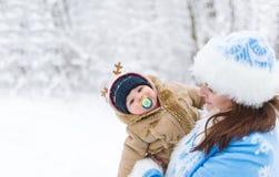 Das Schneemädchen und -Baby, die in einem Winter umfassen, parken unter Baumniederlassungen lizenzfreies stockfoto