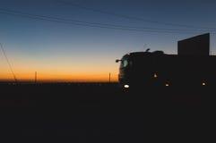 Das Schnellfahren entgegenkommenden von LKWs mit dem Glühen beleuchtet auf der Autobahn nach Sonnenuntergang Lizenzfreie Stockfotos