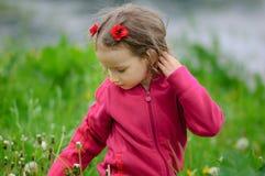 Das Schnittmädchen überprüft sorgfältig den Grashalm und sitzt auf einer Frühlingsreinigung Das Kind kennt die Welt Kinder lizenzfreies stockbild