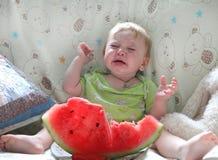 Das schreiende Baby sitzt auf einem Bett in einem hellen Raum Stockbild