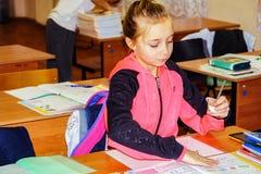 Das Schulmädchen an ihrem Schreibtisch lizenzfreies stockbild
