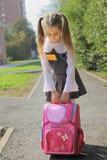 Das Schulmädchen mit einer schweren Schultasche Stockfotos