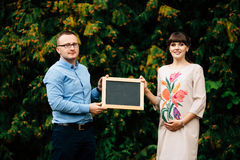 Das schwangere glückliche Paar erwartend, das eine leere Holzkohle hält, verschalen Sie Lizenzfreie Stockfotos