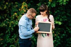 Das schwangere glückliche Paar erwartend, das eine leere Holzkohle hält, verschalen Sie Lizenzfreie Stockbilder