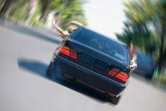 Das schwarze Auto in der Beschleunigung stockbild