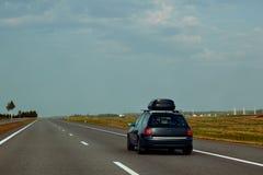Das schwarze Auto mit Dachspitzenfrachtfördermaschinen fährt entlang den Sommer stockbilder