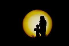 Das schwarze Schattenbild der Mutter und der Kinder, die den Mond aufpassen Stockfoto