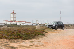 Das Schwarzes Mini Cooper-Auto parkte auf einem Schotterweg vor dem Leuchtturm Stockbild