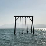 Das Schwingen der hölzerne Kinder steht im blauen ruhigen See unter offenem sauberem Himmel lizenzfreies stockfoto