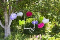 Das Schwingen und die bunten Papierblumen, die am Baum hängen Lizenzfreies Stockbild