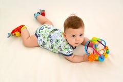 Das Sechsmonats-Baby hält ein Spielzeug auf einem hellen Hintergrund, die Draufsicht Stockfotografie