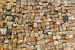 Das Segeltuch der Dorfstraße zeichnete ordentlich mit einem defekten Ziegelstein Stockfotografie