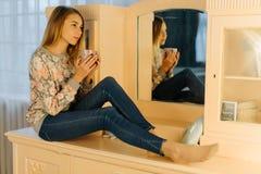 Das Seitenfoto der Jugendlichen, welche die Tasse Tee beim Sitzen auf der Kleidentabelle hält Stockbild
