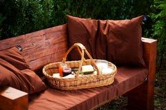 Das selbst gemachte Frühstück auf dem Picknickkorb im Garten Lizenzfreie Stockfotos