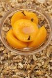 Das selbst gemachte Pfirsichkompott, das mit Nelken in einer Glasschüssel mit Walnussstücken gewürzt wurde, zerstreute herum stockbilder