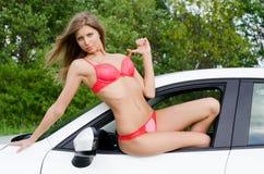 Das sexuelle Mädchen im rosafarbenen Bikini mit weißem Auto Stockbild