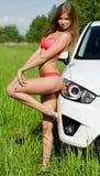 Das sexuelle Mädchen im rosafarbenen Bikini mit weißem Auto Stockfoto