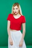 Das sexy junge Mädchen, das rote Spitze und Weiß-Rock trägt, wirft auf grünem Hintergrund auf Porträt von sinnlichem recht blonde Lizenzfreie Stockfotos