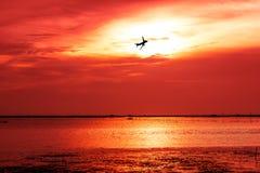das Siluate des Flugzeuges fliegt auf roten und orange Himmel unter SU Lizenzfreie Stockbilder