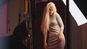 Das sinnliche blonde kaukasische blonde weibliche Modell, das für Fotografen aufwirft - arbeiten Sie Bühne hinter dem Vorhang um Lizenzfreies Stockfoto