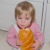 Das Sitzen auf dem Bodenbaby beißt frisches Brot Lizenzfreies Stockbild