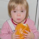 Das Sitzen auf dem Bodenbaby beißt frisches Brot Lizenzfreie Stockbilder