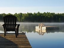 Das Sitzen auf dem Dock am See als der Sonne kommt auf Stockfoto