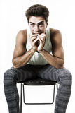 Das sitzende Stillstehen des Jungen stößt auf Beinen, Handvorderer Mund Auf Weiß Lizenzfreies Stockfoto