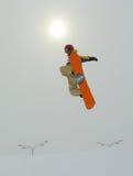 Das Snowboarderspringen und -sonne Lizenzfreie Stockbilder