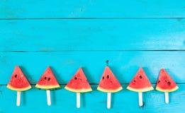 das Sommerwassermelonen-Scheibeneis am stiel auf einer blauen rustikalen Holzrückseite Stockfotografie