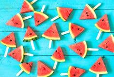 das Sommerwassermelonen-Scheibeneis am stiel auf einer blauen rustikalen Holzrückseite Lizenzfreie Stockfotografie