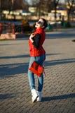 Das sonnige stilvolle Mädchen, das fröhlich, tragende Sonnenbrille lacht, kleidete in einer roten Weste, Denimausstattung, rote K Lizenzfreies Stockbild