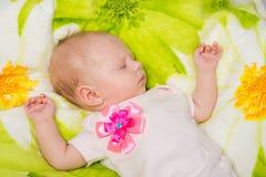 Das sorglose Schlafen des zweimonatigen Babys auf dem Bett Stockbilder
