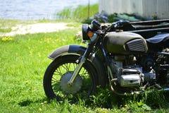 Das Sowjet Dnepr-Motorrad auf dem grünen Gras des Vorderteilabschlusses oben gegen ein sandiges Ufer durch den See lizenzfreies stockbild