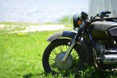 Das Sowjet Dnepr-Motorrad auf dem grünen Gras des Vorderteilabschlusses oben gegen ein sandiges Ufer durch den See stockbilder