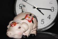 Das Sparschwein mit Bargeld auf dem Hintergrund der Uhr, Zeit ist Geld, lizenzfreies stockfoto