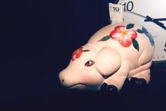 Das Sparschwein mit Bargeld auf dem Hintergrund der Uhr, Zeit ist Geld, stockfotografie