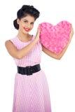 Das spielerische Modell des schwarzen Haares, das ein rosa Herz hält, formte Kissen Lizenzfreie Stockfotografie