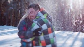 Das spielerische Paar, das Spaß draußen, junges blondes Mädchen hat, wirft oben den Schnee, ihr Freund umarmt sie unter dem Fall  stock video