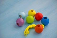 Das Spielzeug der Entwicklungskinder Farbige hölzerne Bälle auf einem Seil Bunte hölzerne Babyperlen für Halskette stockbild