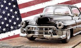 Das Spielzeugauto gegen die amerikanische Flagge Stockfotos