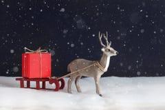 Das Spielzeugrotwild verzögert Schlitten mit einem roten Geschenk Stockfoto