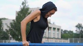 Das sportliche Mädchen, das Trizeps tut, trainieren auf den Strahlen stock footage