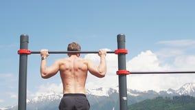 Das Sportmannhandeln zieht Übung auf einer horizontalen Stange gegen einen blauen Himmel hoch stock video