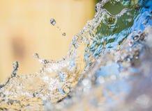 Das Spritzen des klaren Wassers auf Gelb färbt abstrakten Hintergrund Stockfotografie