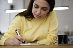 Das starke Hippie-Mädchen kleidete in den Markensweatshirt-Schreibensanmerkungen geschmackvollen Tee trinkend an Lizenzfreie Stockbilder