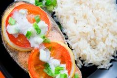 Das Steak des Lachses kochte mit Tomate, Reis, Zwiebel und Zitrone Lizenzfreie Stockbilder