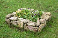 Das Steinbett mit Blumen Stockfotos